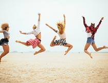 沙滩上开心跳跃的一群美女摄影图片