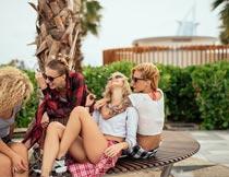 椰树前长椅上休息的美女摄影图片