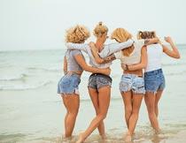 海滩边搂抱的一群美女背影摄影图片