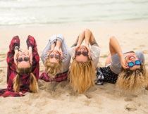 沙滩上弯腰后仰的一群美女摄影图片