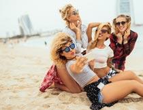 海边沙滩上手机自拍的美女摄影图片