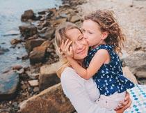 海岸边亲密拥抱亲吻的母女摄影图片