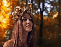 树林里头戴枫叶的长发美女摄影图片
