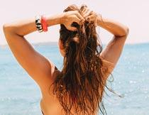 海边双手抓头发的美女背影摄影图片