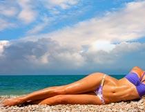 躺在沙滩上的长腿泳装美女摄影图片