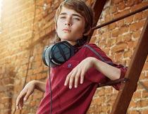靠在梯子上的帅气时尚男孩摄影图片