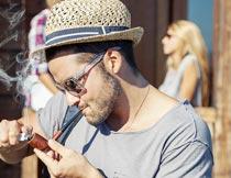 戴着帽子打火机点烟的男人摄影图片