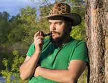 靠着大树烟斗抽烟的男人摄影图片