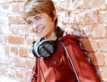 带着耳机靠墙上微笑的男孩摄影图片