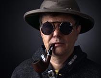 戴帽子墨镜含着烟斗的男士摄影图片