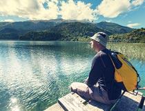坐岸边欣赏湖面风光的男人摄影图片