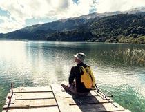 坐在岸边看风景的游客背影摄影图片
