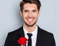 微笑着拿红玫瑰花枝的男人摄影图片