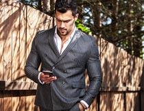 栅栏边看手机的西装男人摄影图片