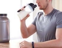 坐桌子前喝牛奶的男士局部摄影图片