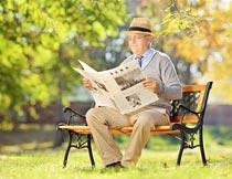 秋天坐椅子上看报纸的男人摄影图片