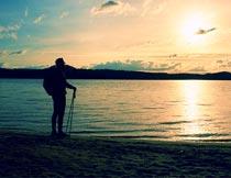 海岸边欣赏美丽日出的男人摄影图片
