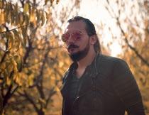 树林里戴墨镜的络腮胡男人摄影图片