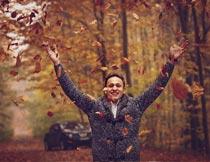 微笑着抛洒秋天落叶的男人摄影图片