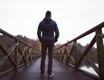 站在木桥梁上的男人背影摄影图片