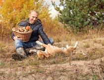 坐在草地上与狗嬉戏的男人摄影图片