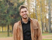 秋天树林里微笑的男人特写摄影图片