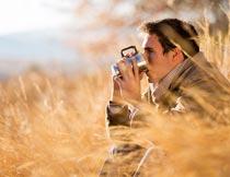草丛中用水杯喝水的男人摄影图片