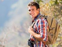背着双肩包和望远镜的男人摄影图片