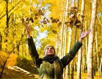 树林里开心抛洒落叶的男人摄影图片