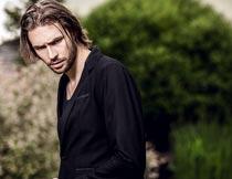 低着头穿黑色西服的帅哥摄影图片