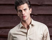 红木板前穿米色衬衫的男人摄影图片