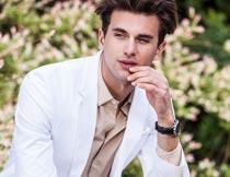 坐木墩上穿白色西服的男人摄影图片