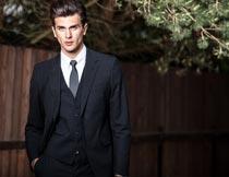 单手插口袋的黑色西服男人摄影图片