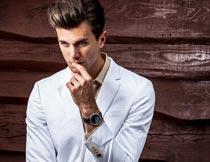 托腮思考的白色西服型男摄影图片