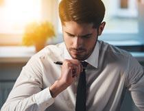 办公桌前看文件的商务男人摄影图片