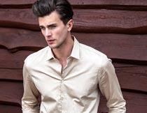 红木板前穿米色衬衫的帅哥摄影图片