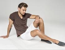 坐地上穿白短裤的英俊男人摄影图片