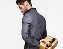 拿礼物放背后的商务男人摄影图片