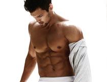 跪在床上的欧美肌肉猛男摄影图片