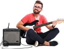 音响和开心弹吉他的男子摄影图片