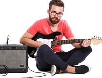 音响旁坐着弹吉他的男子摄影图片