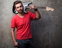 扛着吉他穿红色短袖的男子摄影图片