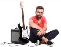 坐在音响吉他旁的欧美帅哥摄影图片