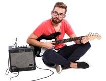 坐音响旁弹吉他的欧美帅哥摄影图片
