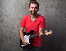 站墙壁前弹吉他的红衣男子摄影图片