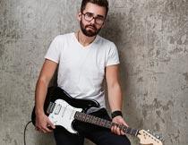 踩着音响弹吉他的白衣男子摄影图片