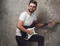 墙壁前开心弹吉他的帅哥摄影图片