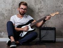坐在地板上弹吉他的帅哥摄影图片