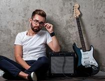 坐音响吉他旁带眼镜的帅哥摄影图片