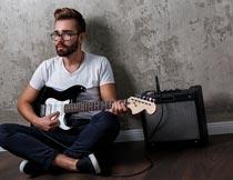 靠着墙壁弹吉他的欧美帅哥摄影图片